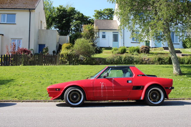 A red sports car on a council estate.