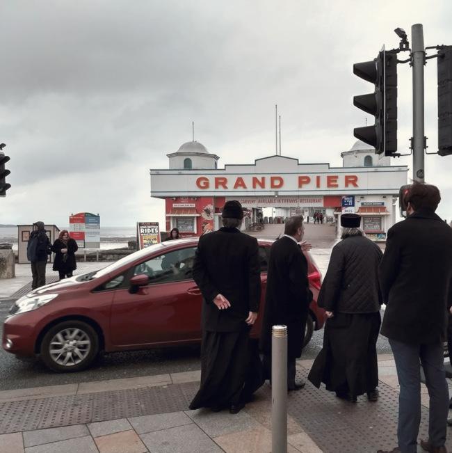 Priests near a pier.