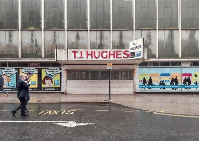 Abandoned retail unit streaked with rain.