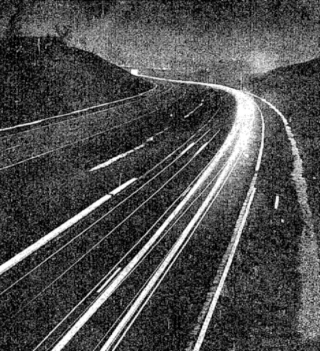 A low resolution image of streaks of light on a curving road.