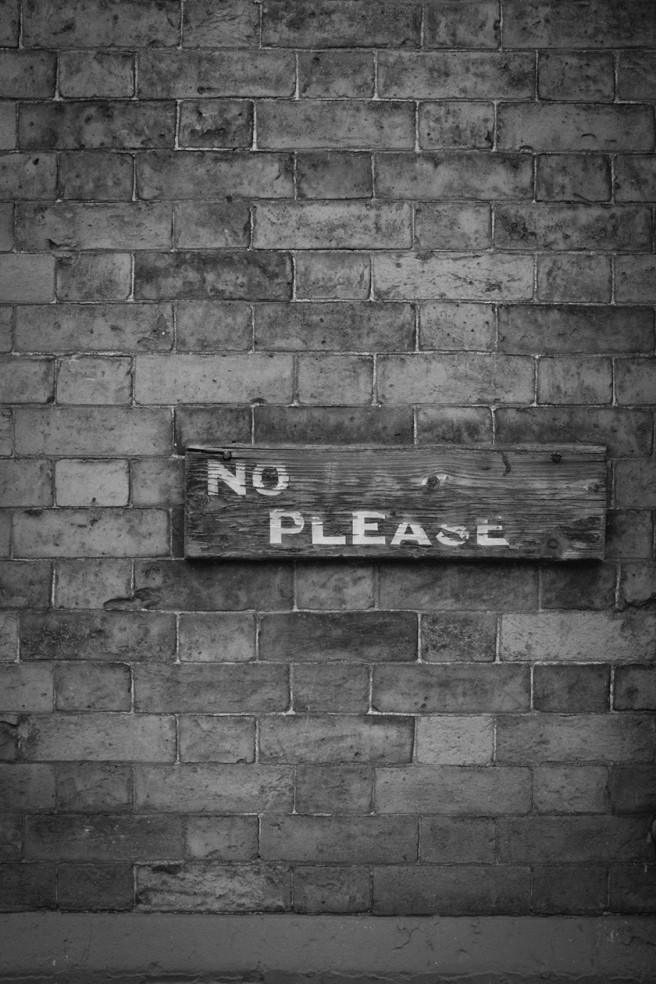 Eroded sign: PLEASE NO....