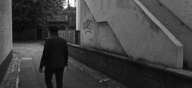 A figure in an alleyway.